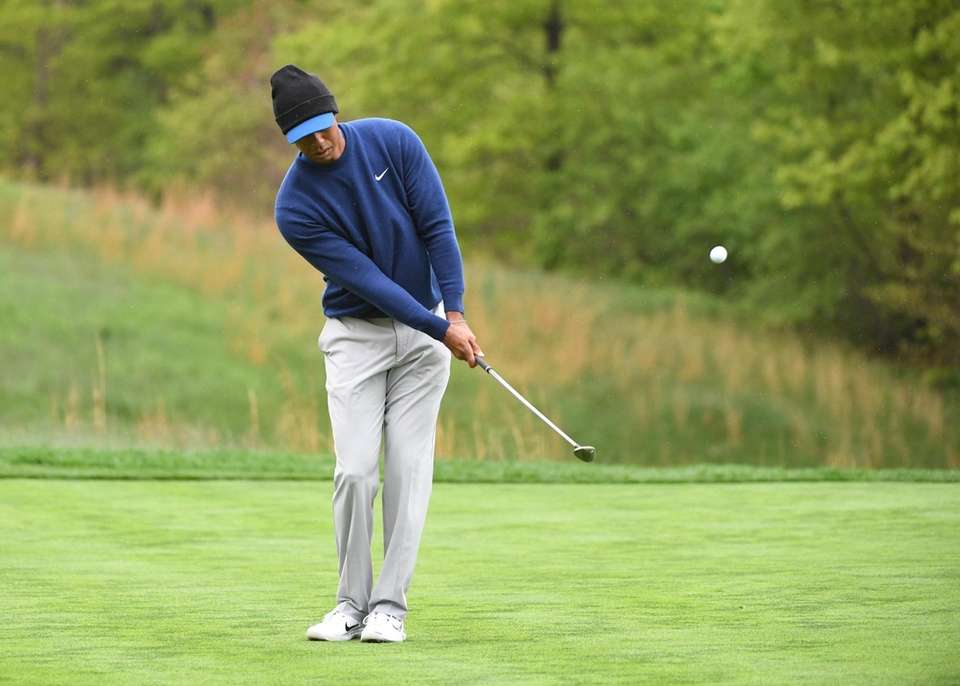 Tiger Woods chips a golf ball during the