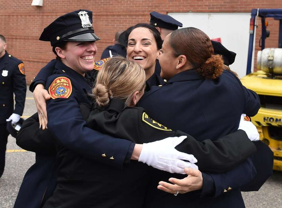 Newly recruited police officers hug one another outside