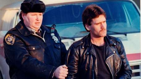 Matthew Solomon, right, is escorted by an officer