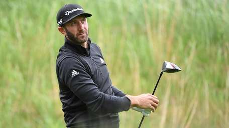 Dustin Johnson watches his tee shot during the