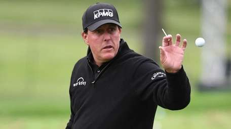 Phil Mickelson catches a ball thrown by his