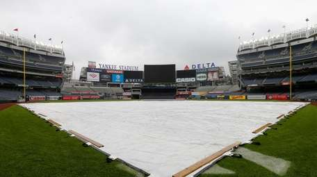 The tarp is seen on the field prior