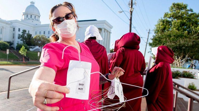 Laura Stiller hands out coat hangers as she