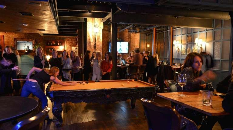 Patrons chat, sip drinks and play billiards inside