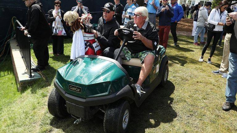 John Daly drives a golf cart during a