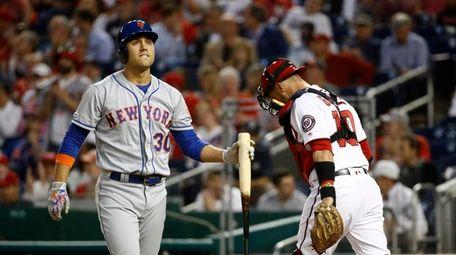 New York Mets' Michael Conforto, left, walks off