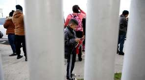 A migrant family waits with others before being