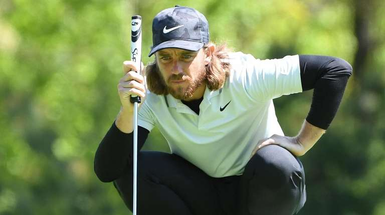 Tommy Fleetwood lines up his putt on the