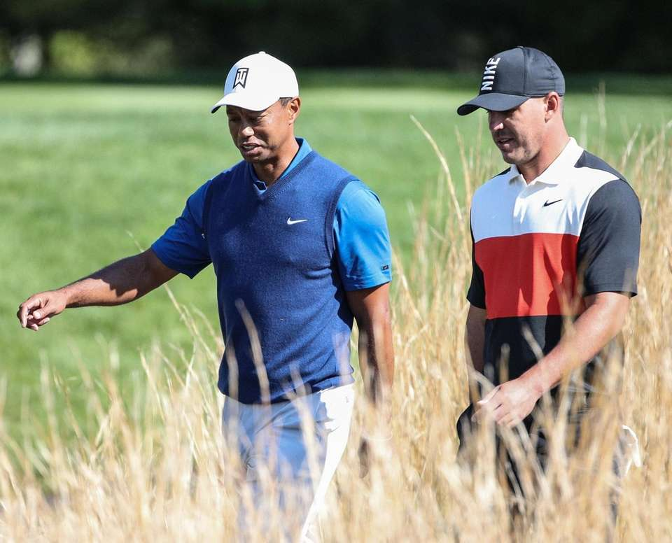 Tiger Woods and Brooks Koepka walk off the