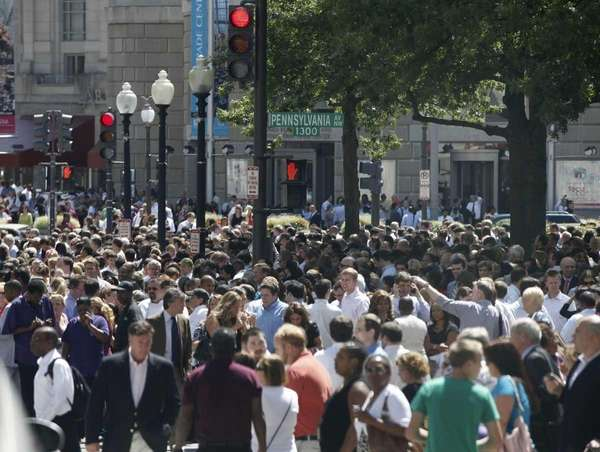 People crowd Pennsylvania Avenue as they evacuate buildings