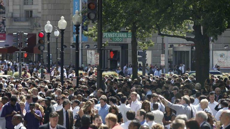 People crowd Pennsylvania Avenue as they evacuate buildings
