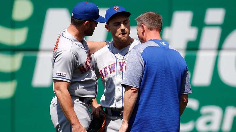 Mets rightfielder Michael Conforto, center, speaks with manager