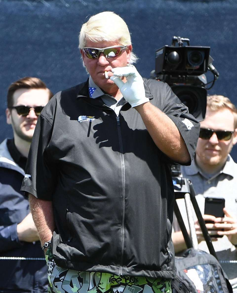 John Daly smokes a cigarette while waiting to