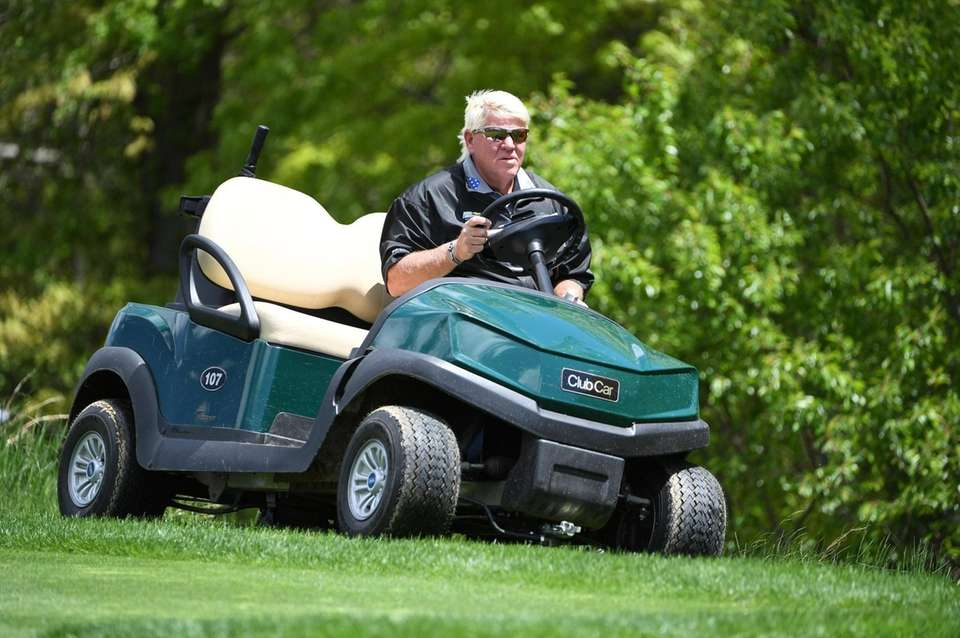 John Daly drives a cart from the 3rd
