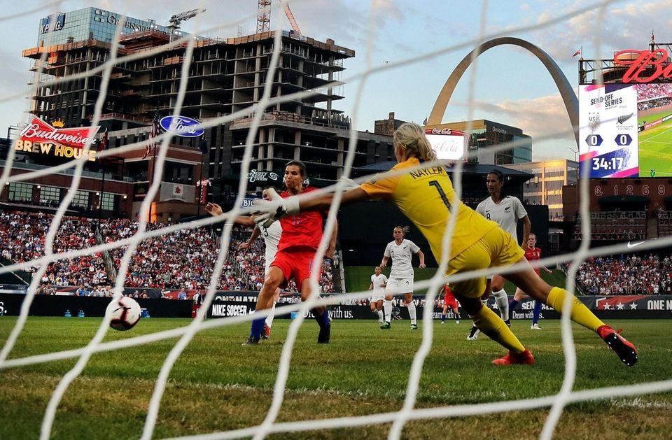 United States forward Tobin Heath, left, scores past