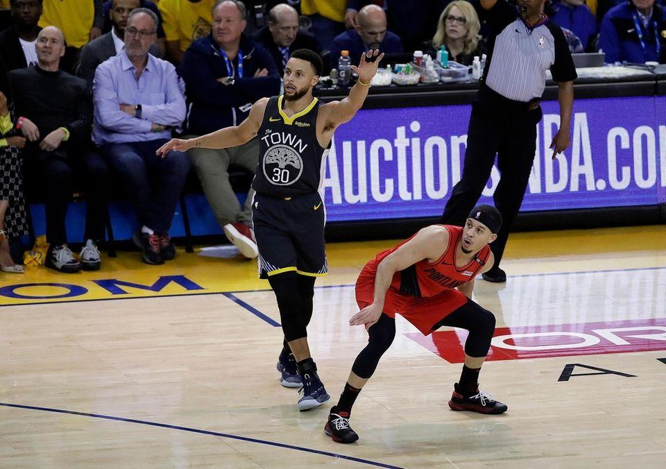 Portland Trail Blazers guard Seth Curry, right, watches