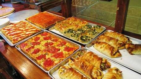 Pies, rolls and calzones behind the counter of