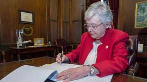 Alabama Gov. Kay Ivey signs a bill that