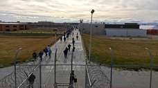 Inmates walk across the grounds of the Idaho
