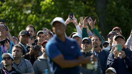 Tiger Woods plays a shot from the 15th
