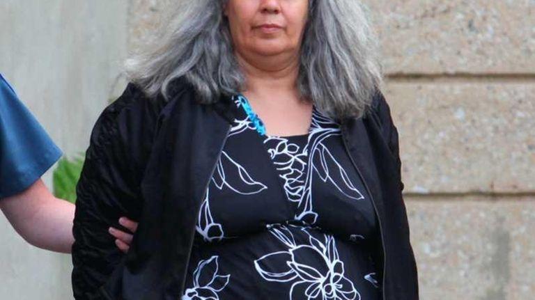 Nassau County police bring Gloria Suarez, 55, out