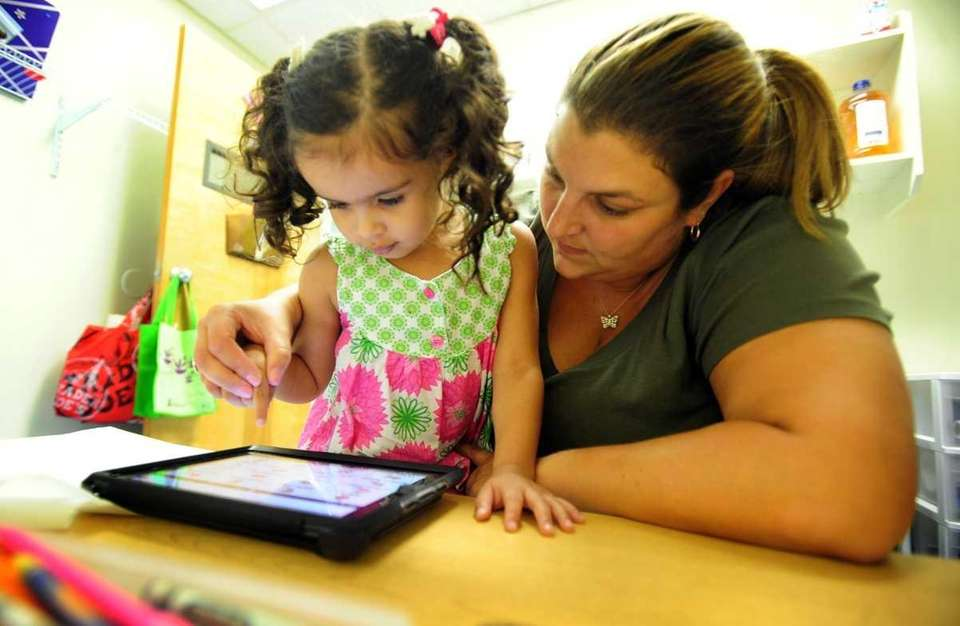 Vanessa Velazquez, 3, works on an iPad with