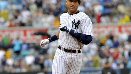 Derek Jeter heads to third base with a