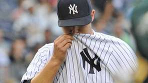 Phil Hughes covers his face as he