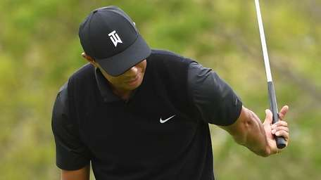 Tiger Woods reacts after he misses a putt
