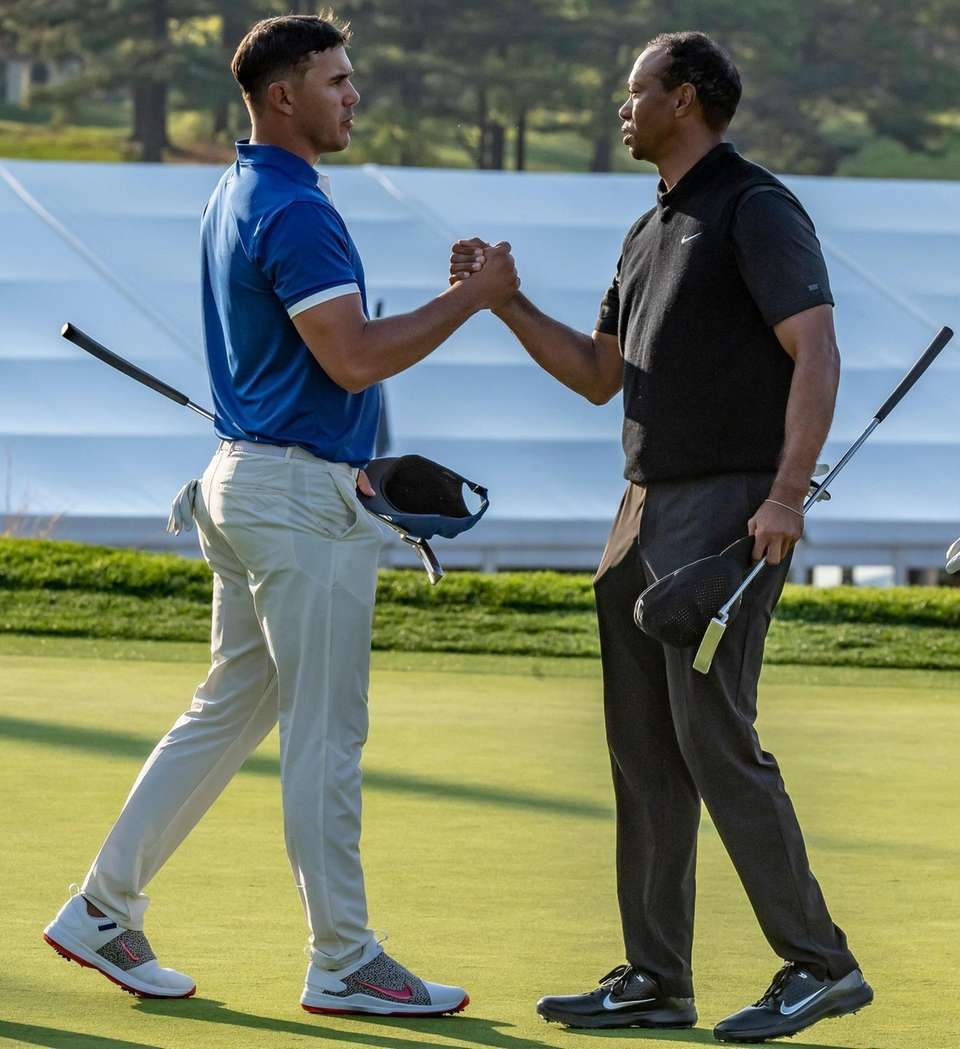 Brooks Koepka and Tiger Woods shake hands and