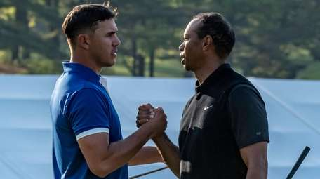 Brooks Koepka and Tiger Woods shake hands at
