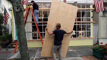 Roman Alvarez (L) and Bob Alvarez use plywood