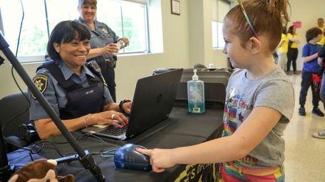 Lia Nicosia, 6, of Bayport has her fingerprints