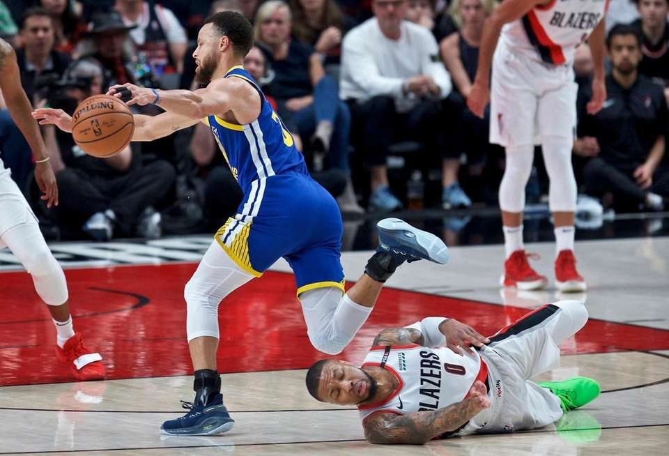 Golden State Warriors guard Stephen Curry, left, trips