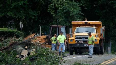 Town of Huntington workers cut up trees downed