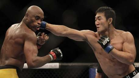Japan's Yushin Okami, right, punches defending middleweight champion