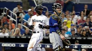 Miami Marlins' Rosell Herrera, left, scores past Mets