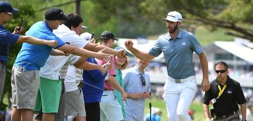 Dustin Johnson greets fans as he approaches the