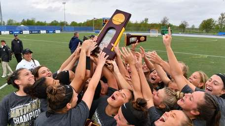 The Adelphi women's lacrosse team celebrates winning the