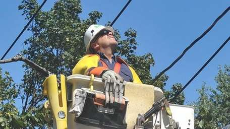 A LIPA lineman works to restore power to
