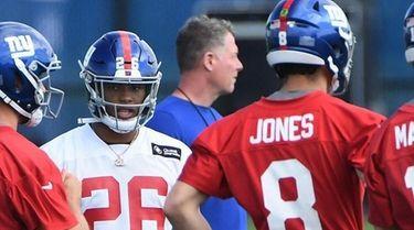 Giants running back Saquon Barkley walks toward quarterback