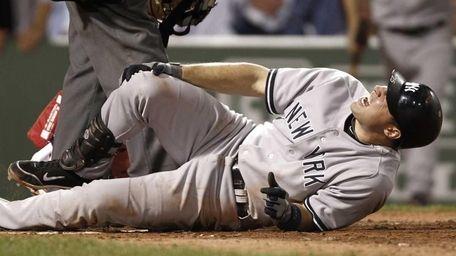 New York Yankees' Mark Teixeira grabs his knee
