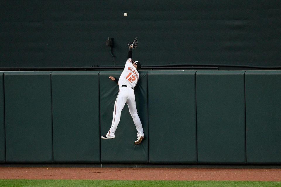 Orioles centerfielder Stevie Wilkerson leaps in vain for