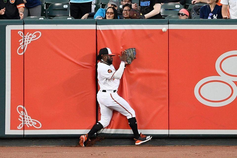 The Orioles' Dwight Smith Jr. slams into the