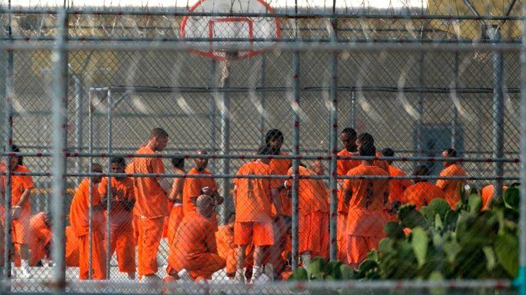 Prison inmates stand in the yard at Arizona