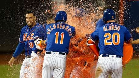 Amed Rosario of the Mets is mobbed by