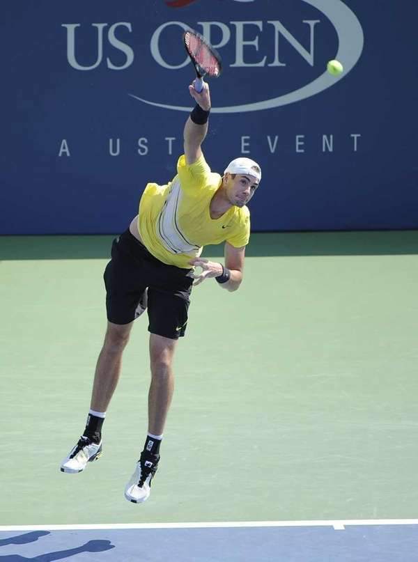 John Isner of the USA serves to Robby