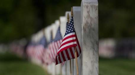 Flags sit in front of graves for Memorial