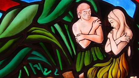 A stained-glass window segment depicts Adam and Eve