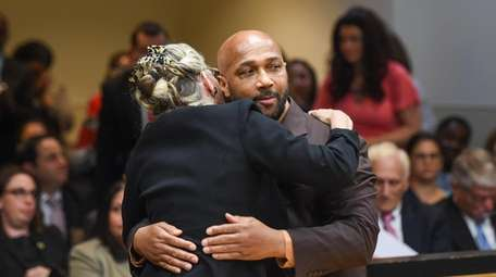 Keith Bush is embraced by his attorney, Adele